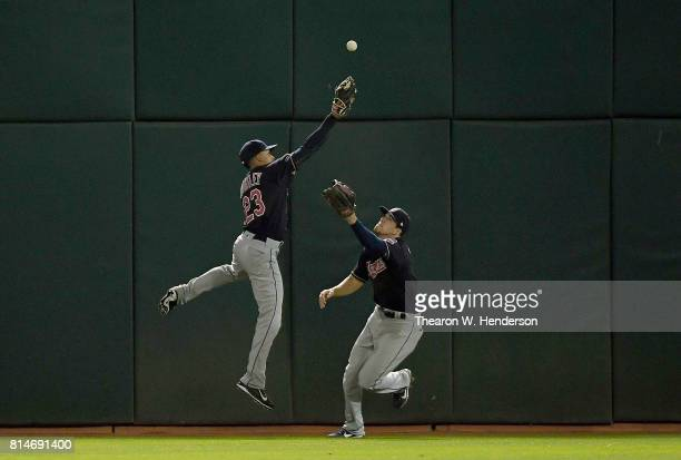 Michael Brantley and Bradley Zimmer of the Cleveland Indians avoid colliding with each other going after a ball that bounces off the wall for a...