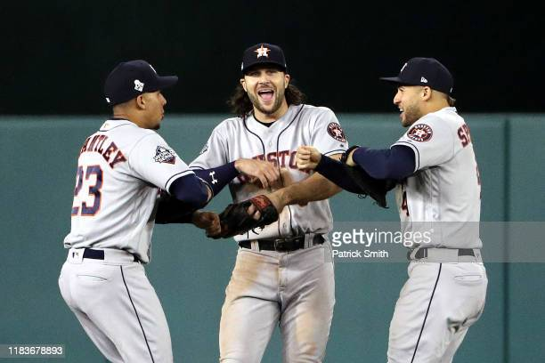 Michael Brantley Jake Marisnick and George Springer of the Houston Astros celebrate their teams 81 win against the Washington Nationals in Game Four...