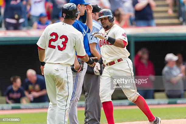 Michael Brantley of the Cleveland Indians and Carlos Santana celebrate after Santana scores on a hit by Ryan Raburn during the fifth inning against...