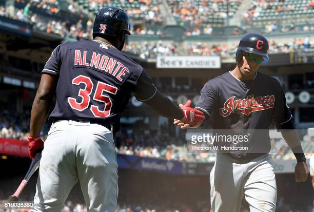 Michael Brantley of the Cleveland Indians is congratulated by Abraham Almonte after scoring against the San Francisco Giants in the top of the eighth...