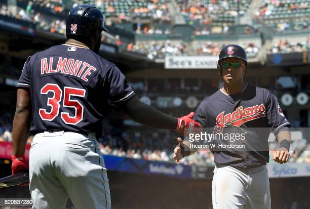 Michael Brantley of the Cleveland Indians is congratulated by Abraham Almonte after Brantley scored against the San Francisco Giants in the top of...