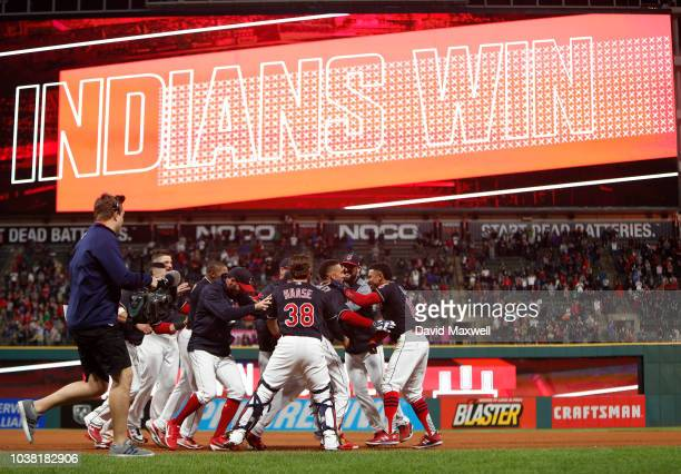 Michael Brantley of the Cleveland Indians is mobbed by teammates as they celebrate after Brantley hit a walk off single against the Boston Red Sox in...