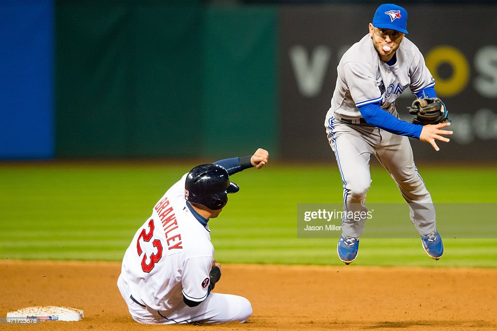 Michael Brantley #23 of the Cleveland Indians is out at second as shortstop Jonathan Diaz #1 of the Toronto Blue Jays throws to first on a ground ball hit by Carlos Santana #41 of the Cleveland Indians during the fifth inning at Progressive Field on April 30, 2015 in Cleveland, Ohio.