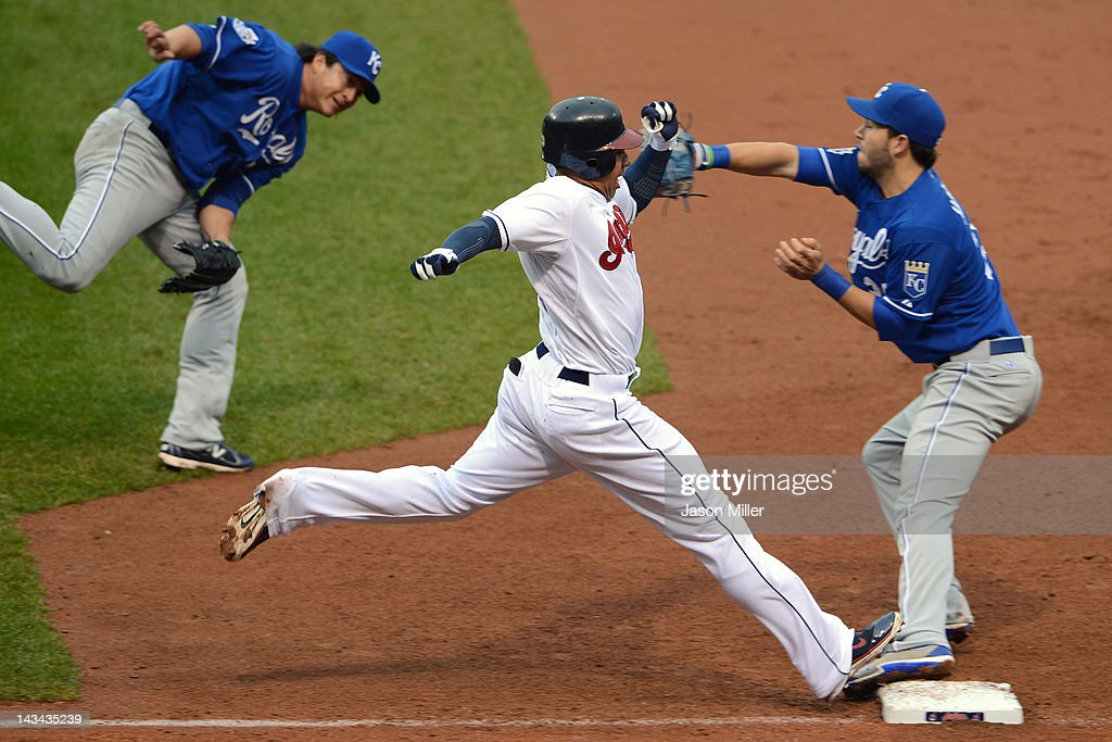 Michael Brantley #23 of the Cleveland Indians is safe as staring pitcher Luis Mendoza #39 flips the ball to first baseman Eric Hosmer #35 of the Kansas City Royals during the sixth inning at Progressive Field on April 26, 2012 in Cleveland, Ohio.