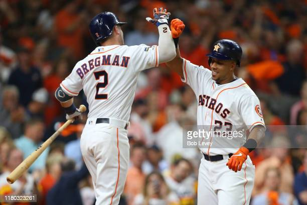 Michael Brantley of the Houston Astros is congratulated by his teammate Alex Bregman after hitting a solo home run against the Tampa Bay Rays during...