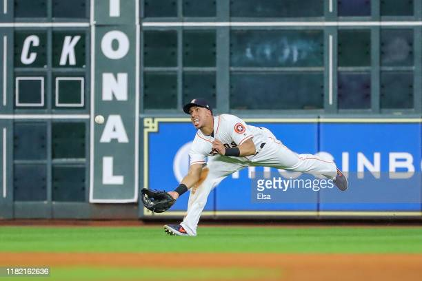Michael Brantley of the Houston Astros makes a diving catch on a fly ball by Aaron Hicks and throws out Aaron Judge for a double play against the New...