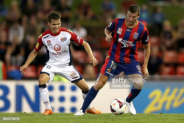 Michael Bridges of the Jets controls the ball ahead of Isaias of Adelaide United during the round 27 ALeague match between the Newcastle Jets and...