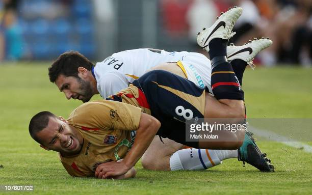 Michael Bridges of the Jets is tackled by Steve Pantelidis of the Gold Coast during the round 18 ALeague match between the Newcastle Jets and Gold...