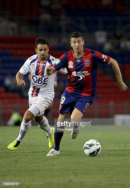 Michael Bridges of the Newcastle Jets controls the ball in front of Travis Dodd of Perth Glory during the round 24 ALeague match between the...