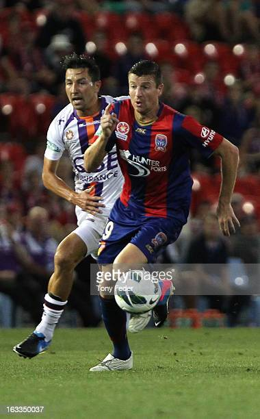 Michael Bridges of the Newcastle Jets controls the ball in front of Jacob Burns of Perth Glory during the round 24 ALeague match between the...