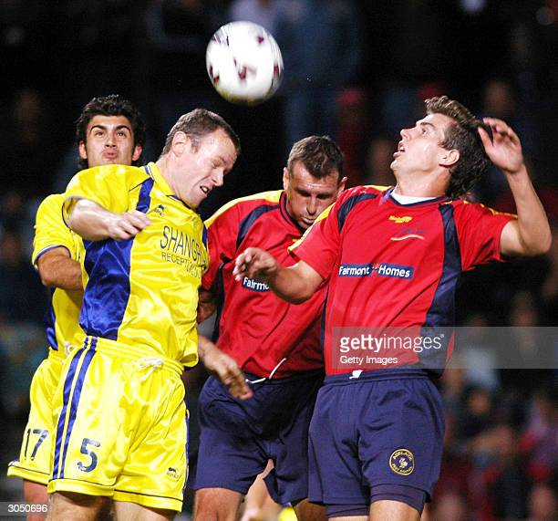 Michael Brooks and Nick Budin of Adelaide contest the ball against player coach Stuart McLaren and Chris Scuderi of Brisbane during the NSL...