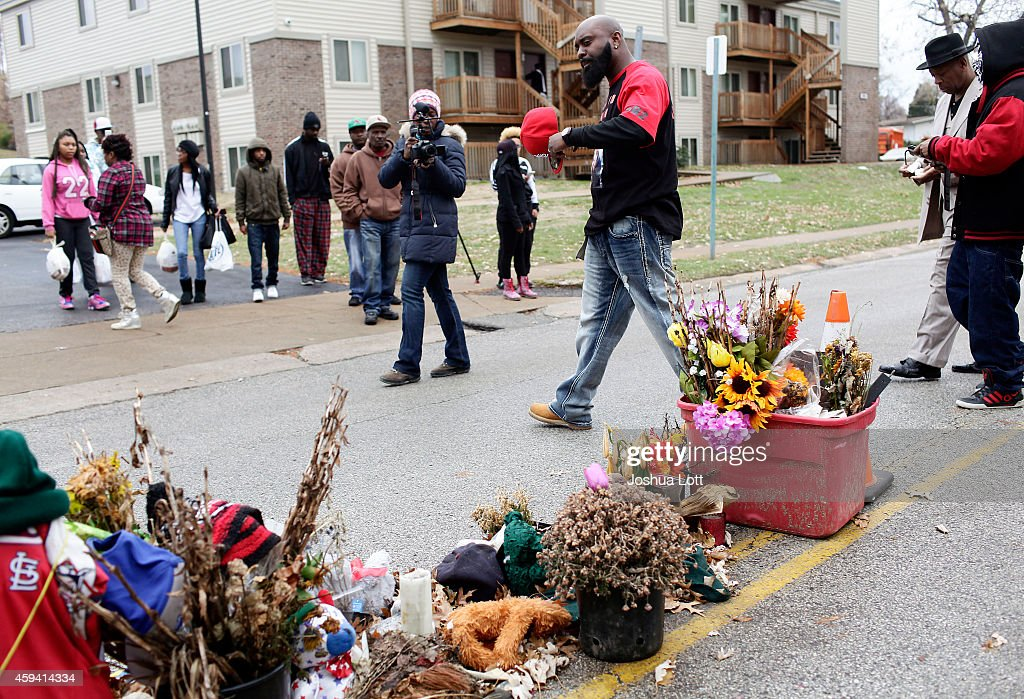 Michael Brown Sr., center, father of Michael Brown, delivers turkeys during an annual Thanksgiving basket give-away as he walks past a memorial for his son November 22, 2014 in Ferguson, Missouri. Michael Brown, a 18-year-old black male teenager was fatally wounded by Darren Wilson, a white Ferguson Police officer on August 9, 2014. A 12-member grand jury is reviewing evidence to decide whether or not to indict Wilson on charges.