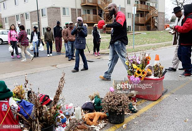 Michael Brown Sr center father of Michael Brown delivers turkeys during an annual Thanksgiving basket giveaway as he walks past a memorial for his...