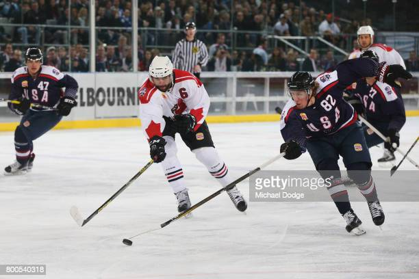Michael Budd of the USA wins the puck from Brett Ponich of Canada during the Ice Hockey Classic match between the United States of America and Canada...