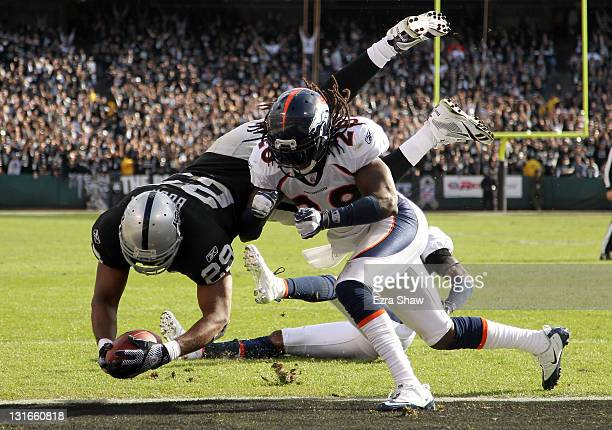 Michael Bush of the Oakland Raiders dives in for a touchdown while being hit by Quinton Carter of the Denver Broncos at Oco Coliseum on November 6...