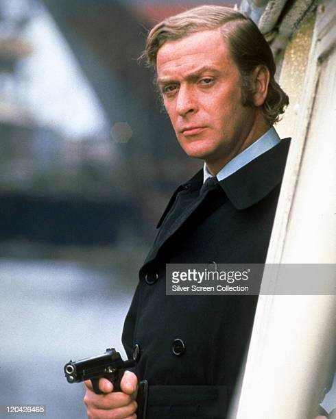 Michael Caine, British actor, wearing a black raincoat and brandishing a handgun in a publicity still issued for the film, 'Get Carter', United...