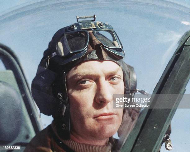 Michael Caine British actor wearing a flying helmet and goggles as he sits in a cockpit of an aircraft in a publicity still issued for the film...