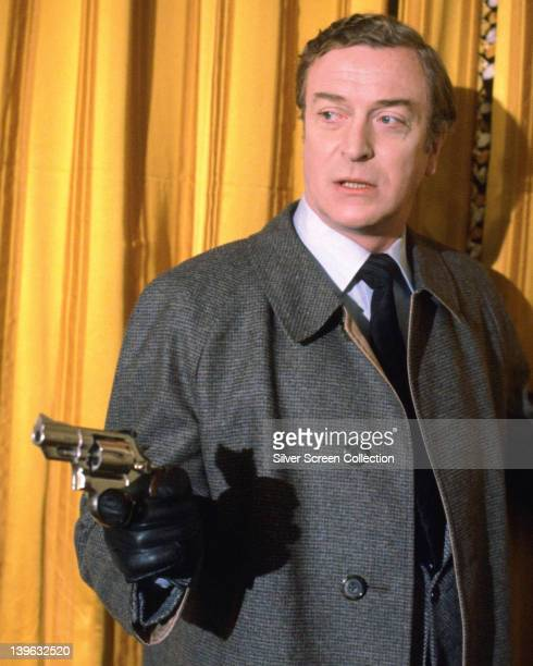 Michael Caine British actor wearing a grey overcoat and black leather gloves pointing a handgun as he stands before a yellow curtain in a publicity...