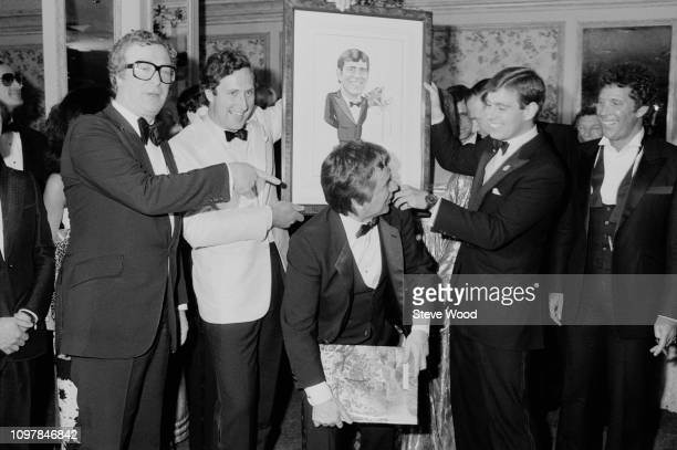 Michael Caine Dudley Moore Tom Jones with Prince Andrew who is holding a cartoon of himself attend gala dinner to honour Prince Andrew by the British...