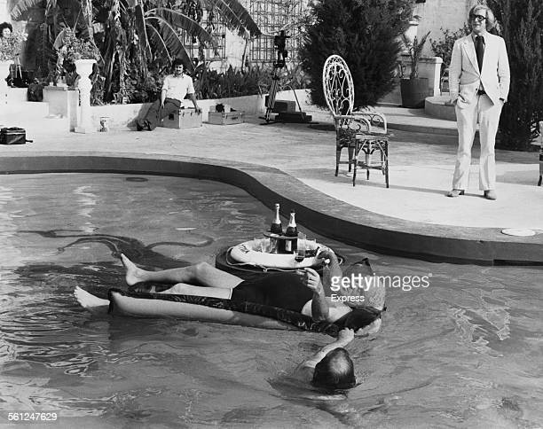 Michael Caine looks on as American actor Lionel Stander floats on a lilo in a swimming pool on the set of Mike Hodges' comedy thriller, 'Pulp',...