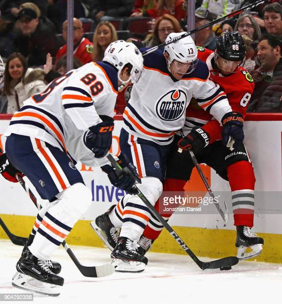 Michael Cammalleri and Brandon Davidson of the Edmonton Oilers battle for the puck with Patrick Kane of the Chicago Blackhawks at the United Center...