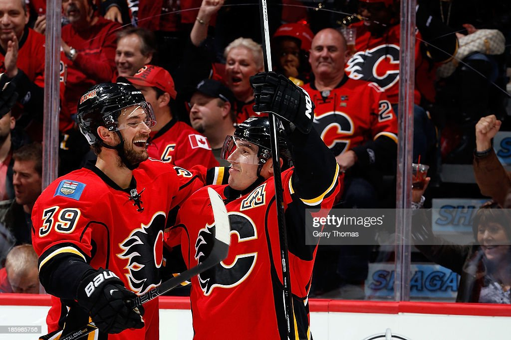 Michael Cammalleri #13 and TJ Galliardi #39 of the Calgary Flames celebrate a goal against the Washington Capitals at Scotiabank Saddledome on October 26, 2013 in Calgary, Alberta, Canada.