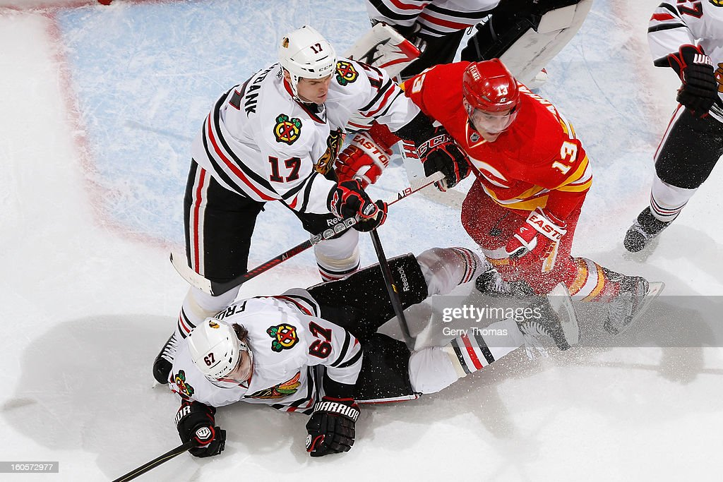 Michael Cammalleri #13 of the Calgary Flames skates against Sheldon Brookbank #17 and Michael Frolik #67 of the Chicago Blackhawks on February 2, 2013 at the Scotiabank Saddledome in Calgary, Alberta, Canada.