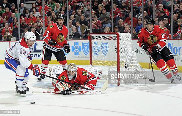 Michael Cammalleri of the Montreal Canadiens turns toward the puck as Chicago Blackhawks goalie Corey Crawford sprawls out onto the ice and Brent...