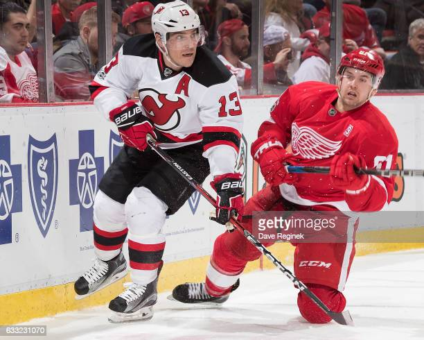 Michael Cammalleri of the New Jersey Devils skates along the boards followed by Xavier Ouellet of the Detroit Red Wings during an NHL game at Joe...