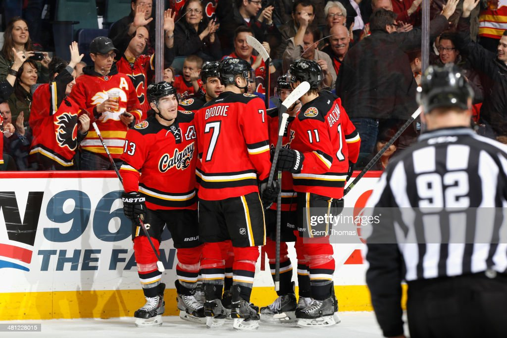 Michael Cammalleri #13, T.J. Brodie #7, Mikael Backlund #11 and Mark Giordano #5 of the Calgary Flames celebrate a goal against the New York Rangers at Scotiabank Saddledome on March 28, 2014 in Calgary, Alberta, Canada.