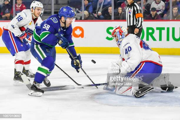 Michael Carcone of the Utica Comets takes a shot on Michael McNiven of the Laval Rocket while Kenny Agostino of the Laval Rocket follows close by at...