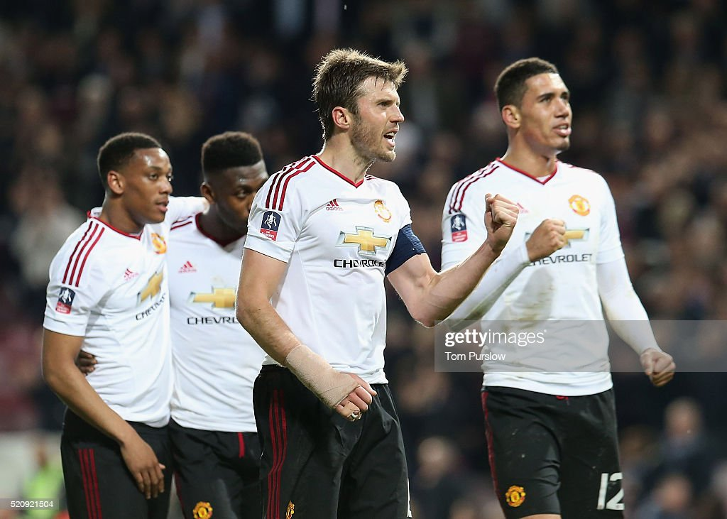 Michael Carrick and Chris Smalling of Manchester United celebrate after the Emirates FA Cup Sixth Round replay match between West Ham United and Manchester United at Boleyn Ground on April 13, 2016 in London, England.