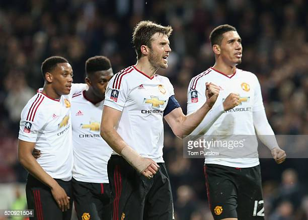 Michael Carrick and Chris Smalling of Manchester United celebrate after the Emirates FA Cup Sixth Round replay match between West Ham United and...