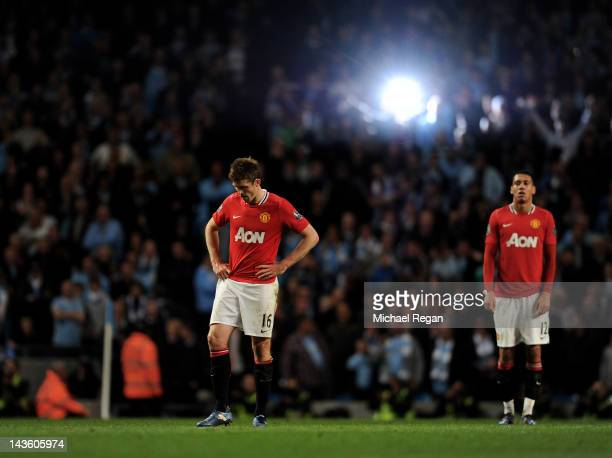 Michael Carrick and Chris Smalling of Manchester United look dejected at the end of the Barclays Premier League match between Manchester City and...