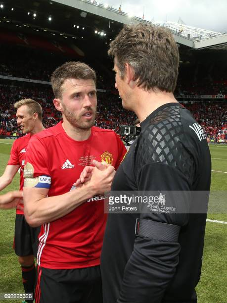 Michael Carrick of Manchester United '08 XI speaks to Edwin van der Sar after the Michael Carrick Testimonial match between Manchester United '08 XI...