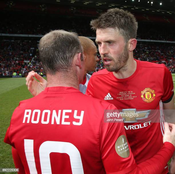 Michael Carrick of Manchester United '08 XI speaks to Wayne Rooney after the Michael Carrick Testimonial match between Manchester United '08 XI and...