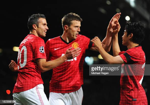 Michael Carrick of Manchester United celebrates with Robin van Persie and Shinji Kagawa as he scores their first goal during the UEFA Champions...