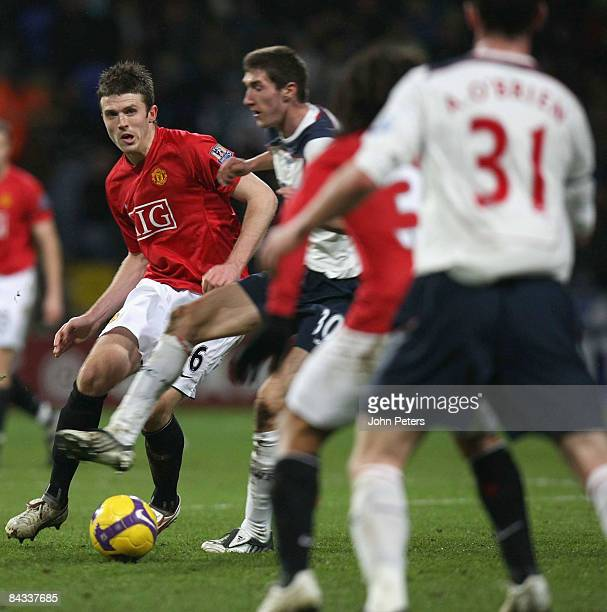 Michael Carrick of Manchester United clashes with Chris Basham of Bolton Wanderers during the Barclays Premier League match between Bolton Wanderers...