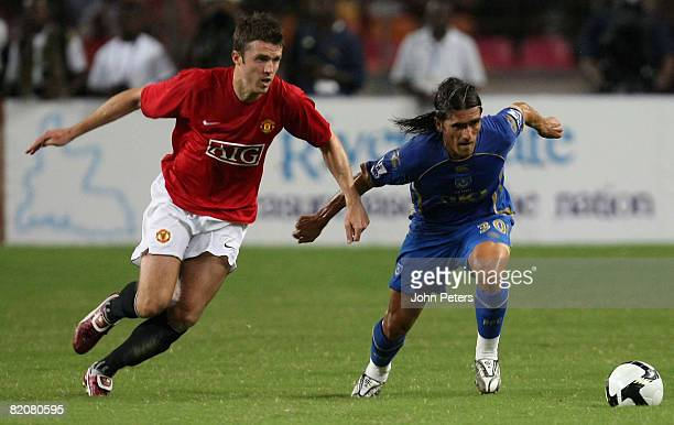 Michael Carrick of Manchester United clashes with Pedro Mendes of Portsmouth during the preseason friendly match between Manchester United and...