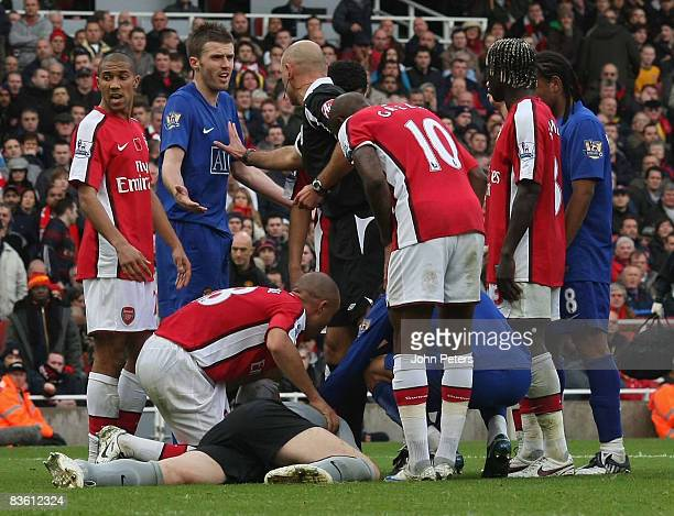 Michael Carrick of Manchester United complains to referee Howard Webb while Manuel Almunia of Arsenal lies injured during the Barclays Premier League...
