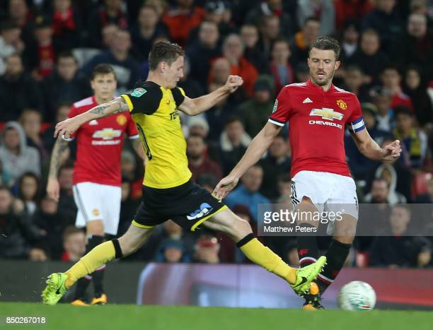 Michael Carrick of Manchester United in action with Joe Mason of Burton Albion during the Carabao Cup Third Round between Manchester United and...