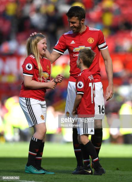 Michael Carrick of Manchester United shows appreciation to the fans during the lap of honour with his family after the Premier League match between...