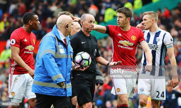 Michael Carrick of Manchester United speaks to referee Mike Dean at half time during the Premier League match between Manchester United and West...