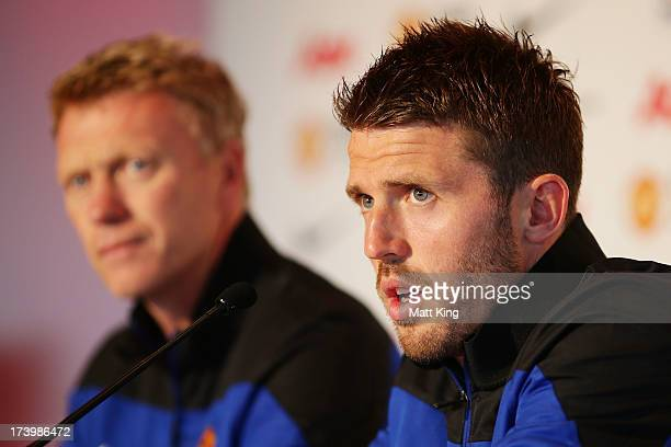 Michael Carrick speaks to the media as Manchester United manager David Moyes looks on during a Manchester United press conference at Museum of...