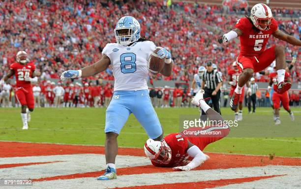 Michael Carter of the North Carolina Tar Heels beats Dexter Wright of the North Carolina State Wolfpack for a touchdown during their game at Carter...