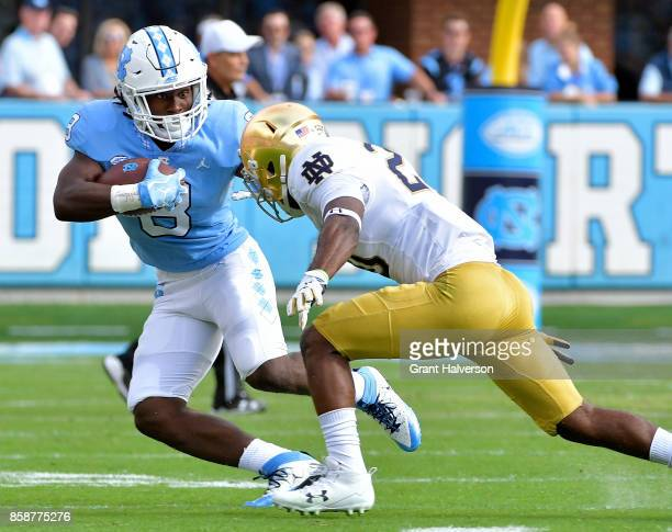 Michael Carter of the North Carolina Tar Heels runs against Shaun Crawford of the Notre Dame Fighting Irish during the game at Kenan Stadium on...