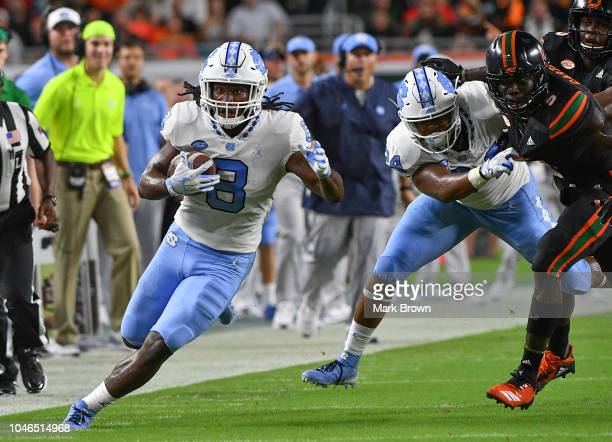 Michael Carter of the North Carolina Tar Heels runs with the ball against the Miami Hurricanes at Hard Rock Stadium on September 27 2018 in Miami...