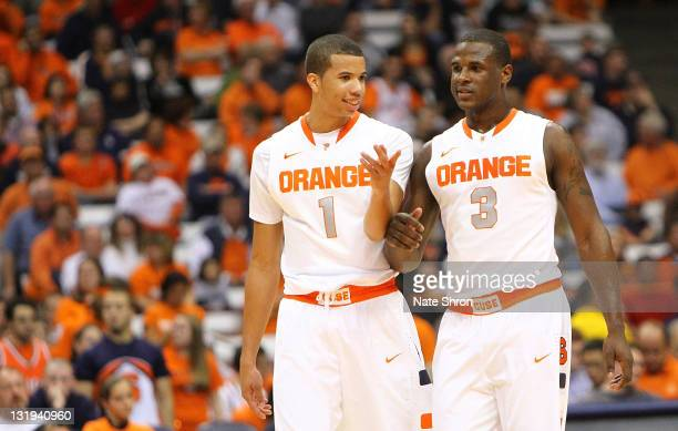 Michael CarterWilliams and Dion Waiters of the Syracuse Orange talk on the court in between plays during the game against the College of Saint Rose...
