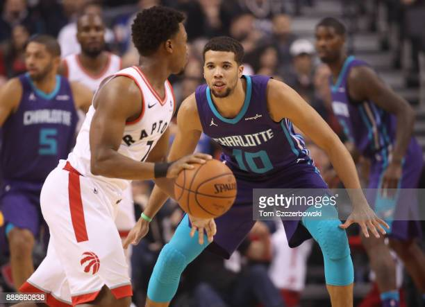 Michael CarterWilliams of the Charlotte Hornets defends against Kyle Lowry of the Toronto Raptors during NBA game action at Air Canada Centre on...