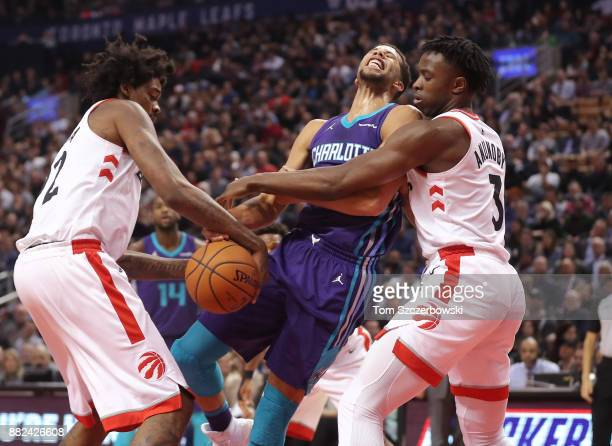 Michael CarterWilliams of the Charlotte Hornets loses the ball to Lucas Nogueira and OG Anunoby of the Toronto Raptors during NBA game action at Air...
